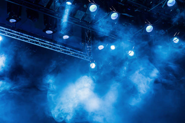 Blue light rays from the spotlight through the smoke at the theater or concert hall. Lighting equipment for a performance or show stock photo