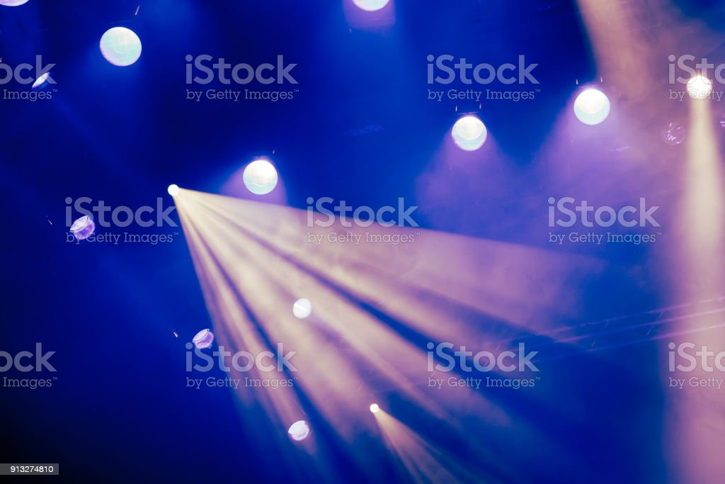 Blue light rays from the spotlight through the smoke at the theater...