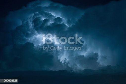 istock Blue Lightning strike surrounded by storm clouds. 1060628328