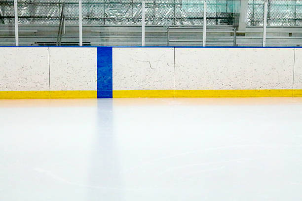 Blue line, boards and bleachers at a ice hockey rink Photograph from the center of the ice at a ice hockey rink.  The blue line is on the boards and in the ice of the indoor arena.  Through the glass, metal bleachers can be seen in this small town ice rink.  The boards are covered with black marks from pucks and is lined with a yellow stripe. ice rink stock pictures, royalty-free photos & images