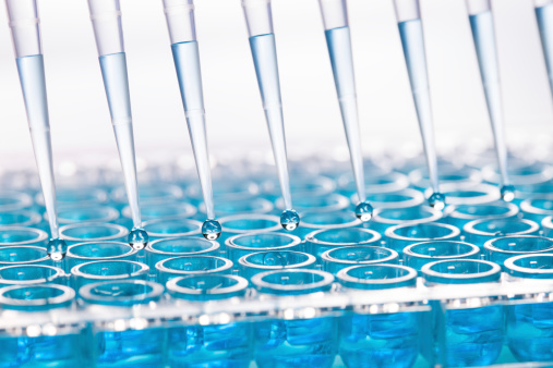 istock Blue liquid dripping from funnel into test tubes 175239030