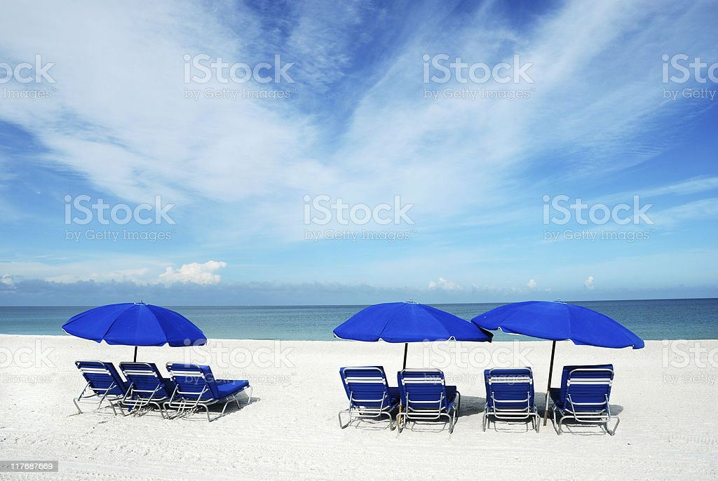 Blue lounge chairs and sun umbrellas on a white sand beach stock photo