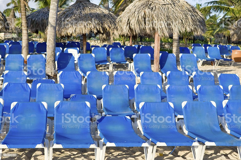 Blue lounges on a sand beach royalty-free stock photo