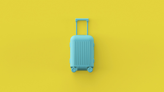 Blue luggage bag, cabin baggage on yellow background, traveling summer concept. Stylish vacation suitcase, pastel colors, summertime tourist background with space for text. Tourism conceptual design.