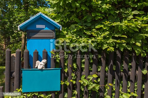 A mailbox with a sitting white angel at a wooden fence