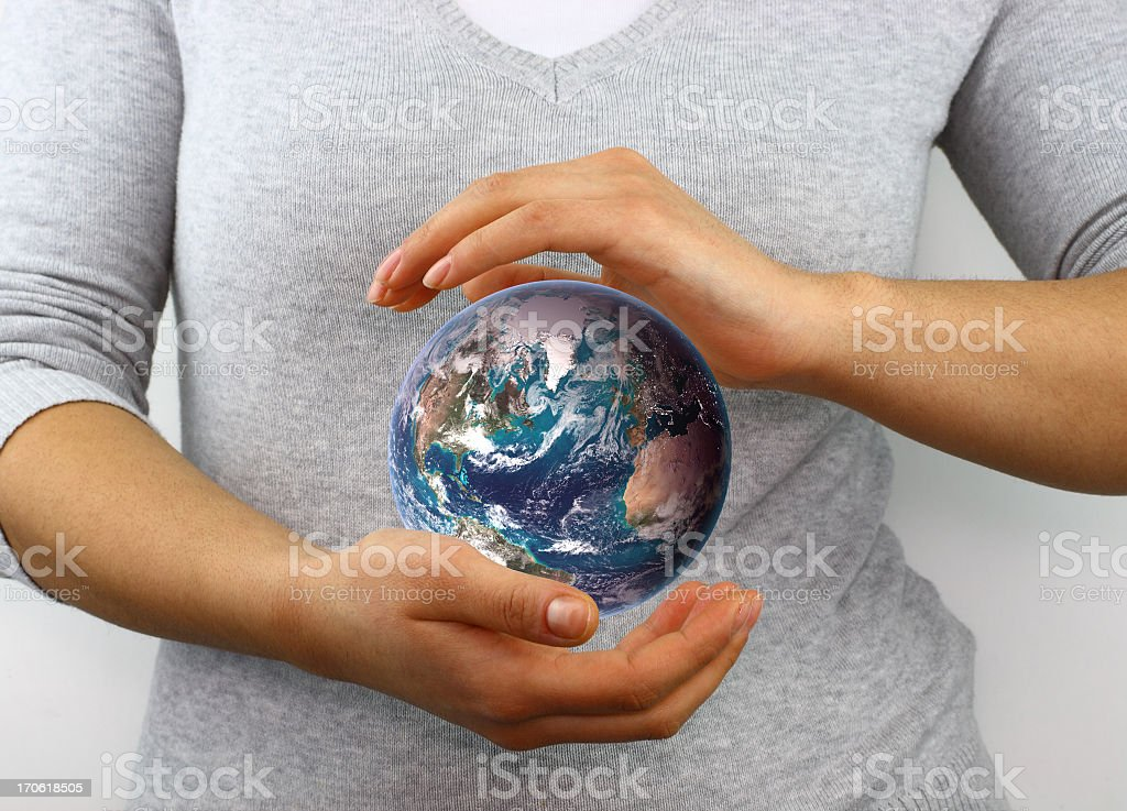 Blue marble between hands royalty-free stock photo