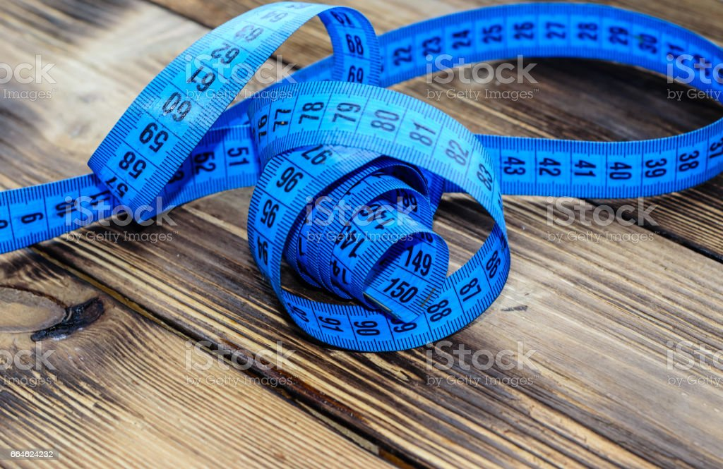 Blue measuring tape on wooden background stock photo