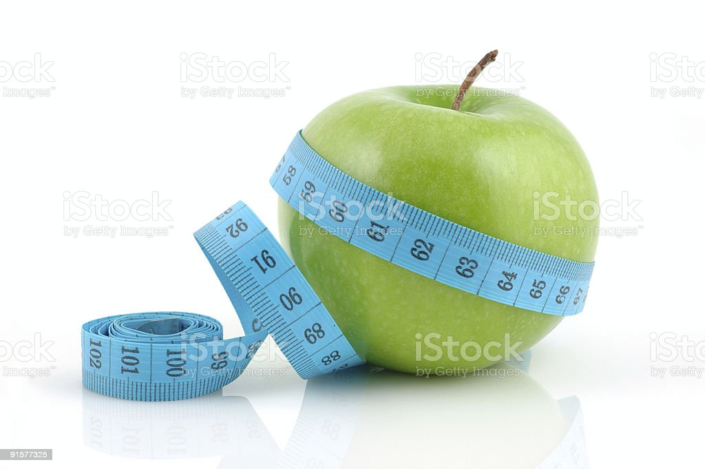 A blue measuring tape wrapped around a Granny Smith Apple royalty-free stock photo