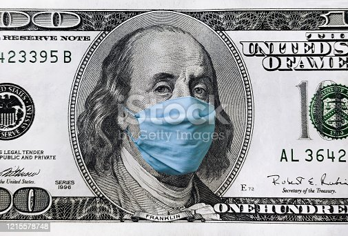 Blue medical mask on the face of Benjamin Franklin with a hundred dollar bill. The concept of the global economic crisis associated with the coronavirus quarantine COVID-19.