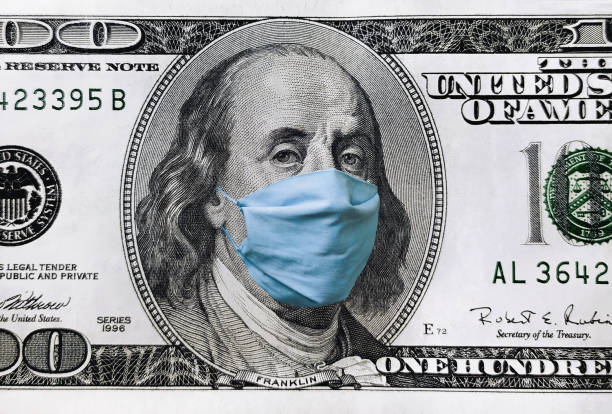 Blue medical mask on the face of Benjamin Franklin with a hundred dollar bill. The concept of the global economic crisis associated with the coronavirus quarantine COVID-19. Blue medical mask on the face of Benjamin Franklin with a hundred dollar bill. The concept of the global economic crisis associated with the coronavirus quarantine COVID-19. benjamin franklin stock pictures, royalty-free photos & images
