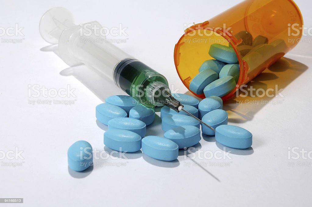 Blue medical pills and syringe on white background stock photo