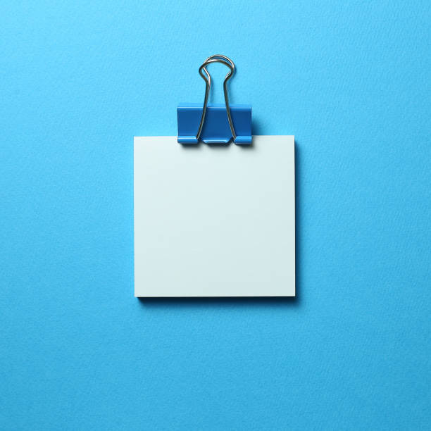 Blue memo pad sticky note and clip on blue background stock photo