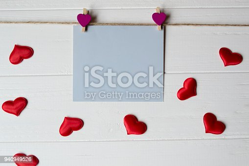 istock Blue memo sheet fastened with a decorative pin on a white wooden board. 940949526