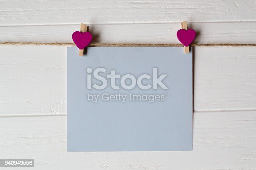 istock Blue memo sheet fastened with a decorative pin on a white wooden board. 940949556