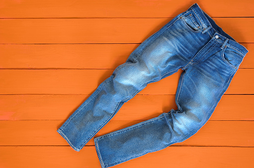 istock Blue mens jeans denim pants on orange background. Contrast saturated color. Fashion clothing concept. View from above 915923400