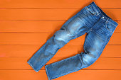 Blue mens jeans denim pants on orange background. Contrast saturated color. Fashion clothing concept. View from above