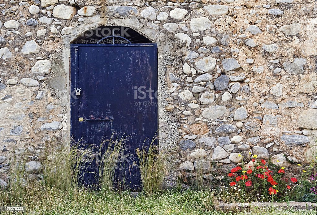 Blue metallic door on stone building stock photo