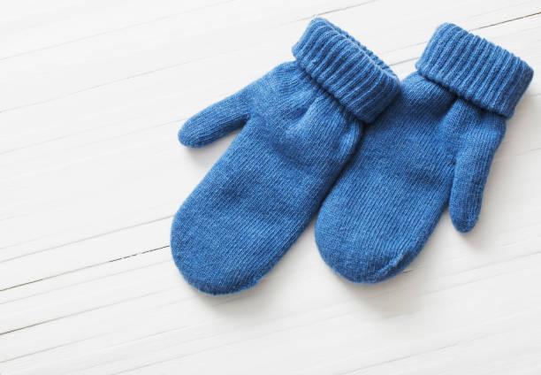 blue mittens on white wooden background - mitene imagens e fotografias de stock