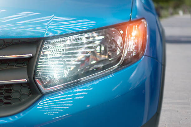 Blue modern car closeup of headlight Blue modern car closeup of headlight. Exterior detail, shallow depth of field. headlight stock pictures, royalty-free photos & images