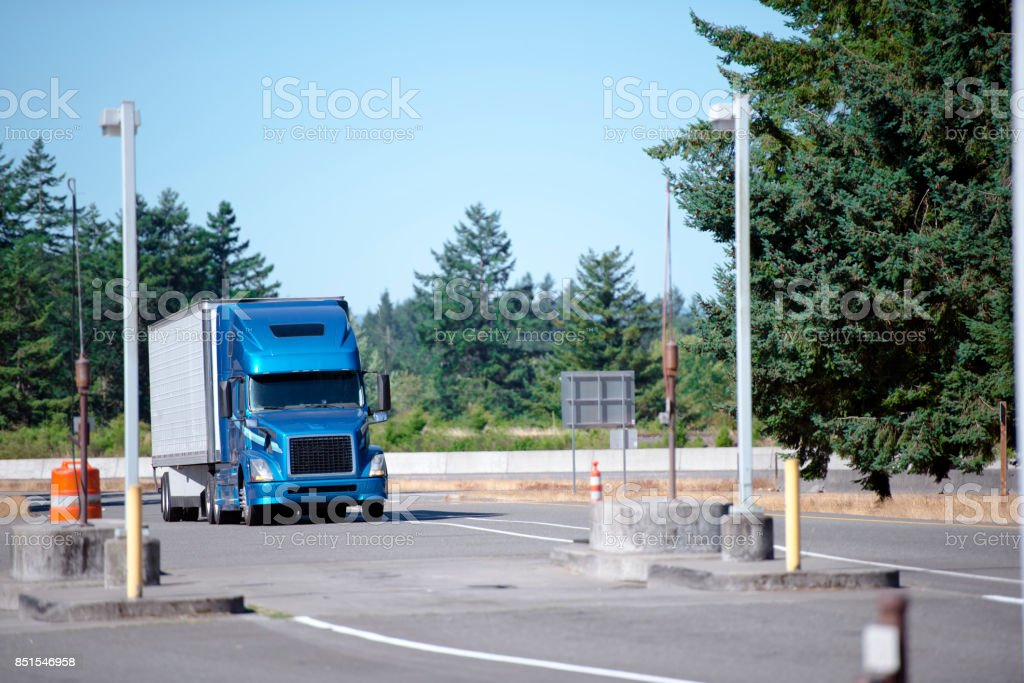 Blue modern semi truck with trailer running to rest area entrance with green trees stock photo