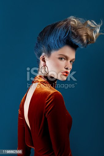 Young woman with blue mohawk wearing orange velvet dress