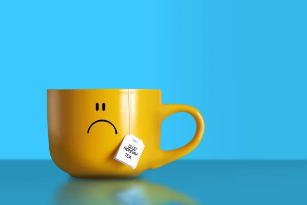 tè blu del lunedì. grande tazza gialla triste. - blue monday foto e immagini stock