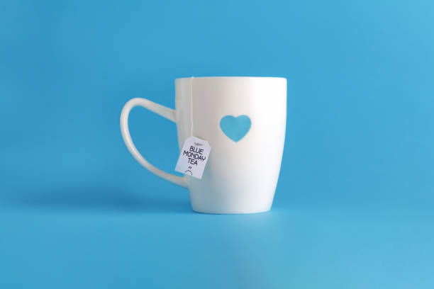 tè blu del lunedì. tazza bianca su blu. - blue monday foto e immagini stock