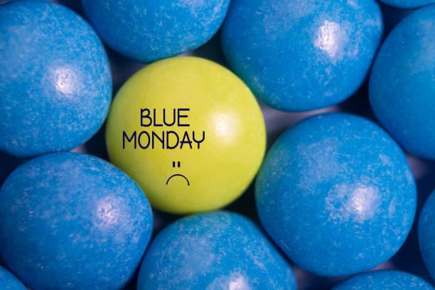 testo del lunedì blu. caramelle gialle in blu. - blue monday foto e immagini stock