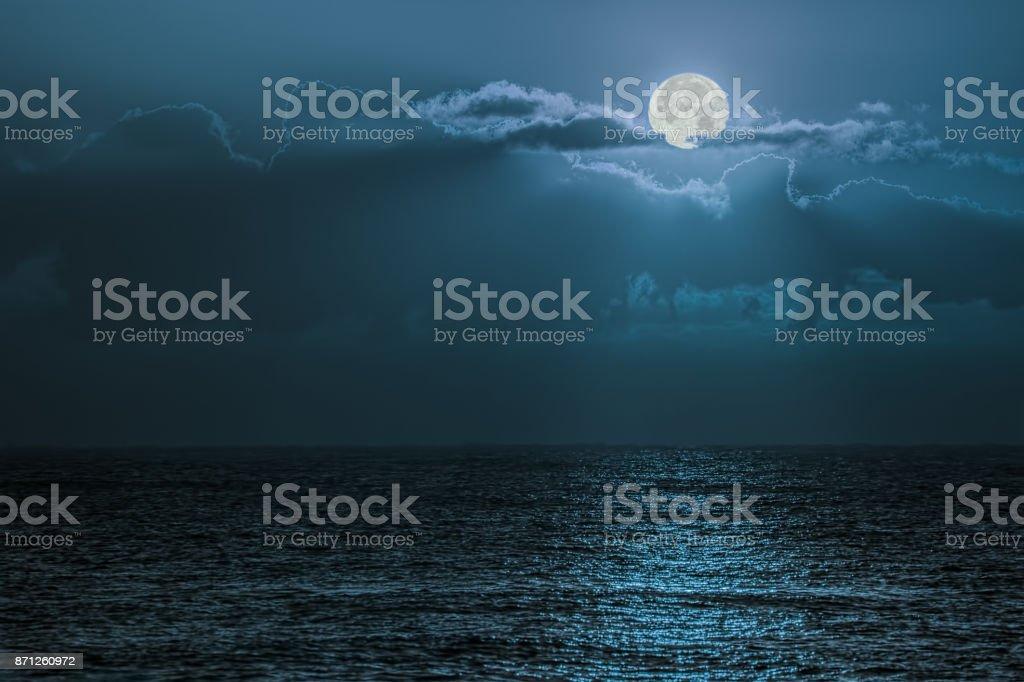 Blue moon light reflecting off ocean. Romantic twilight moonlight...