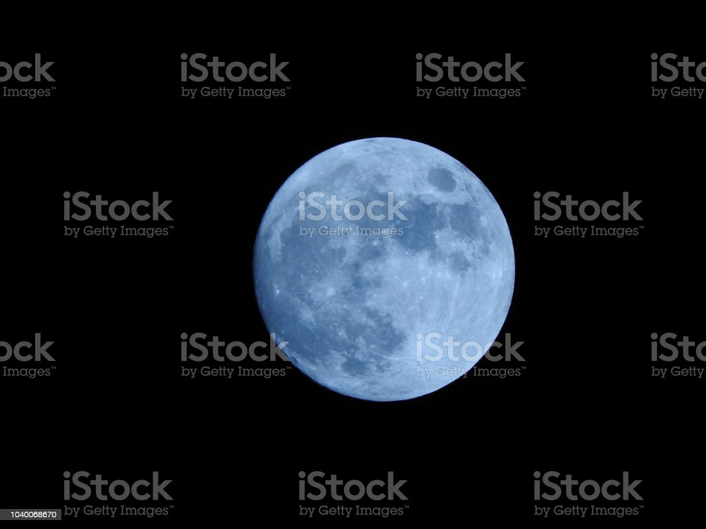Close view of the moon with details of the surface in a blue light