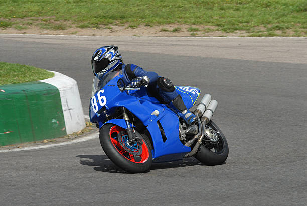 A blue motorcycle racer on a race track stock photo
