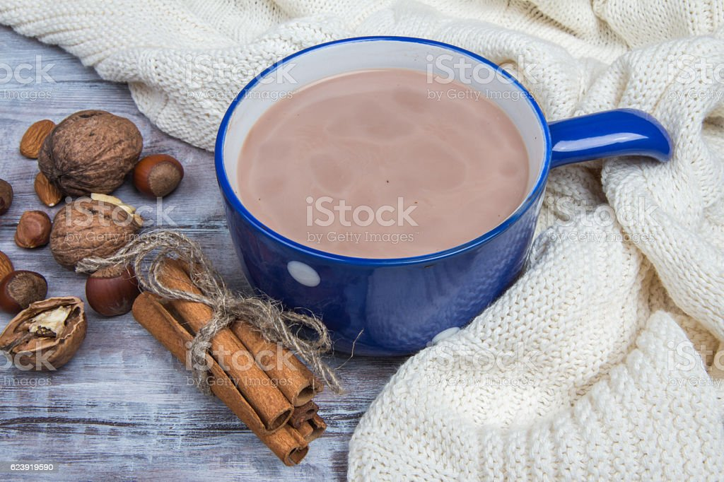 Blue mug of hot chocolate, nuts on white knitted plaid. stock photo