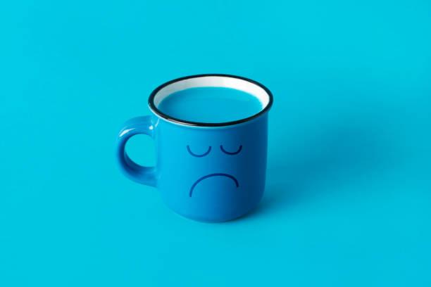blue mug with a sad face stock photo
