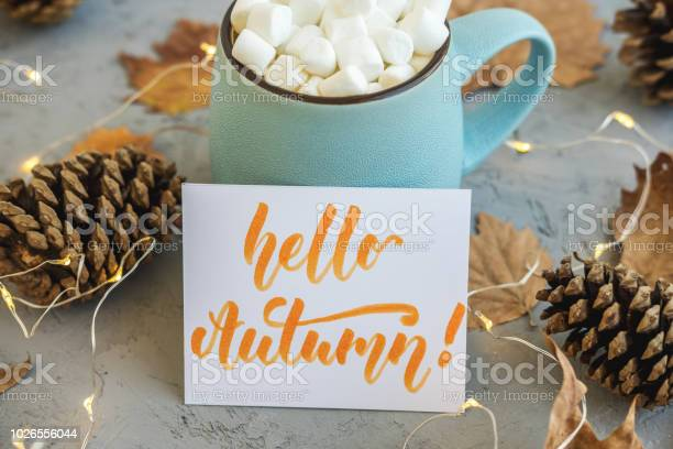 Photo of Blue mug with coffee, hot chocolate or cocoa with marshmallow on gray concrete background and lying dry leaves, cones, garland, sign Hello Autumn. Concept of warm cozy autumn.