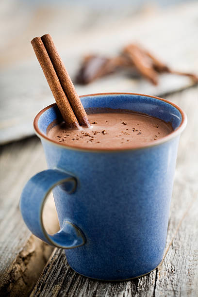 Blue mug with hot chocolate and cinnamon sticks stock photo