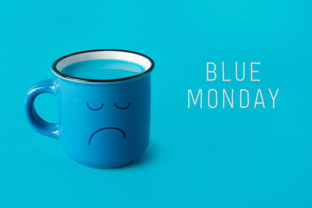 blue mug with sad face and text blue monday stock photo