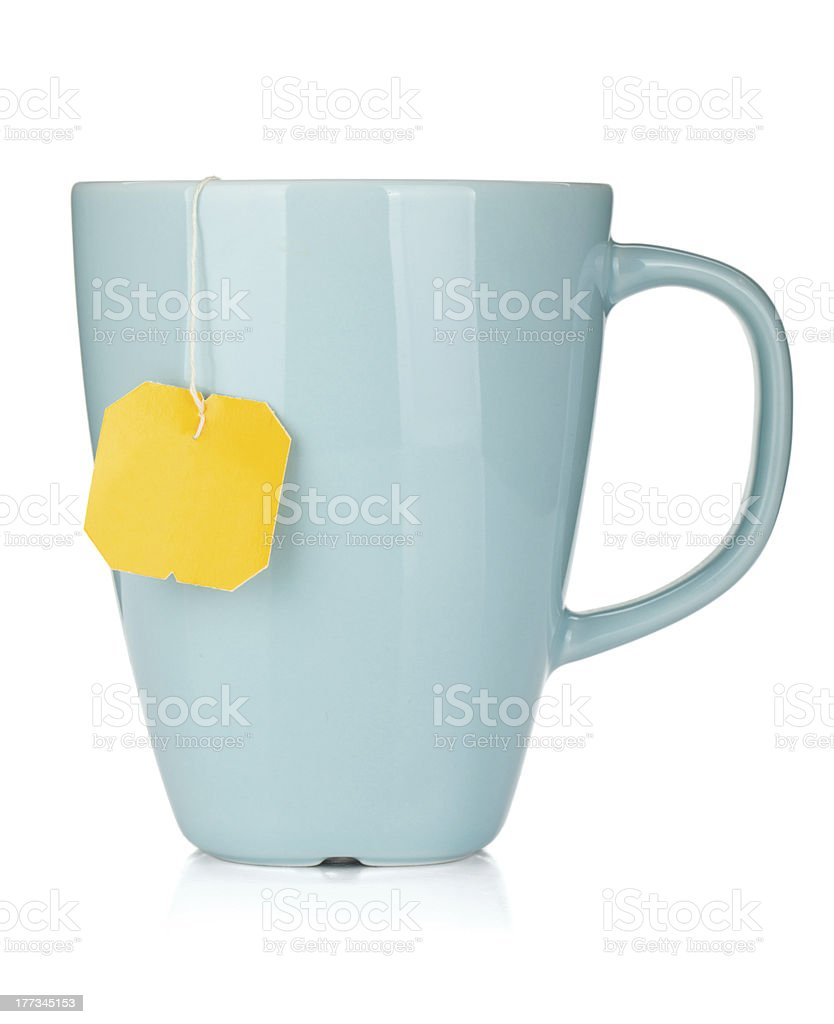 Blue mug with yellow teabag tag hanging out stock photo