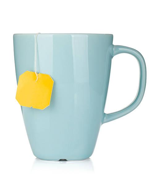 blue mug with yellow teabag tag hanging out - theekop stockfoto's en -beelden