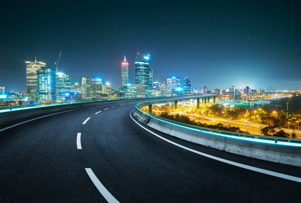 Blue neon light design highway overpass with modern city background . Night scene . stock photo