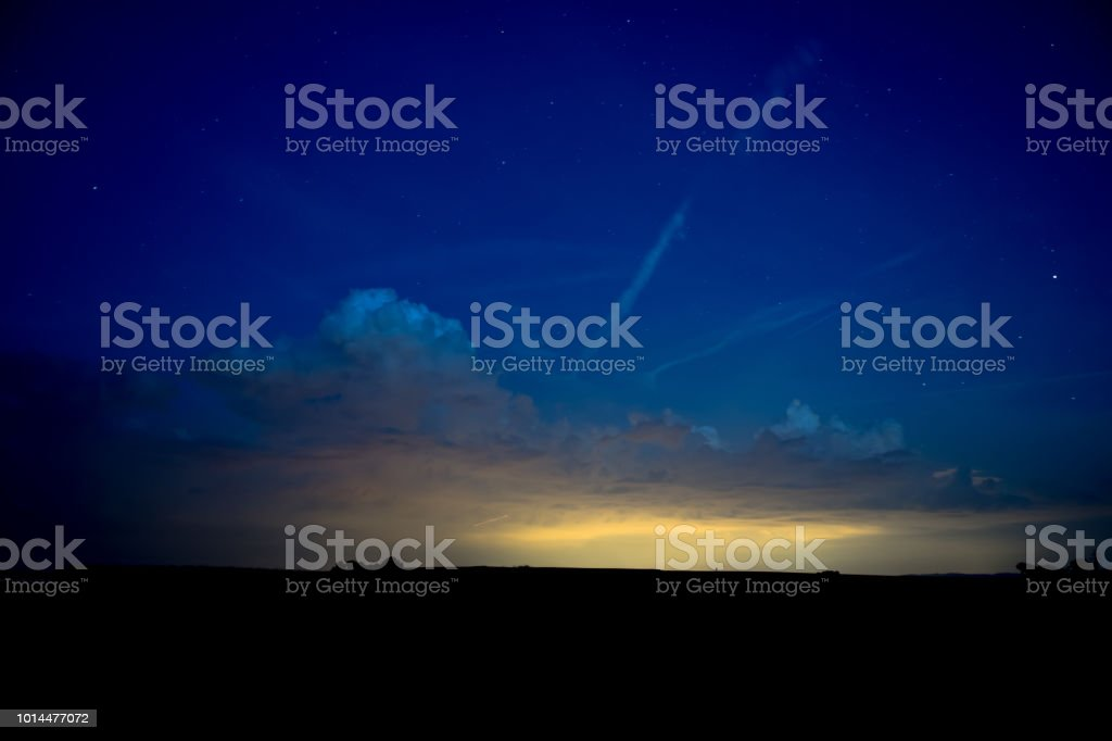 Blue Nightsky with Stars and Clouds over Silhouette Landscape stock photo