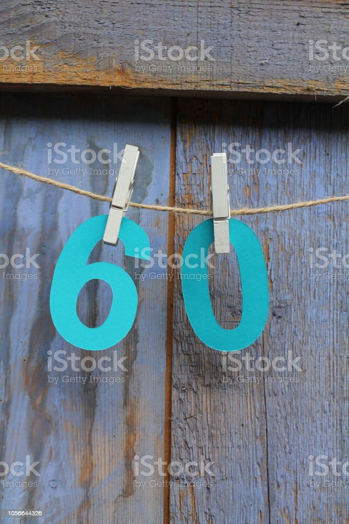 Blue number 60 pegged on string stock photo
