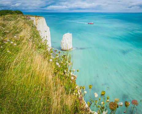 Blue ocean boat white cliffs sea stacks Jurassic Coast Dorset