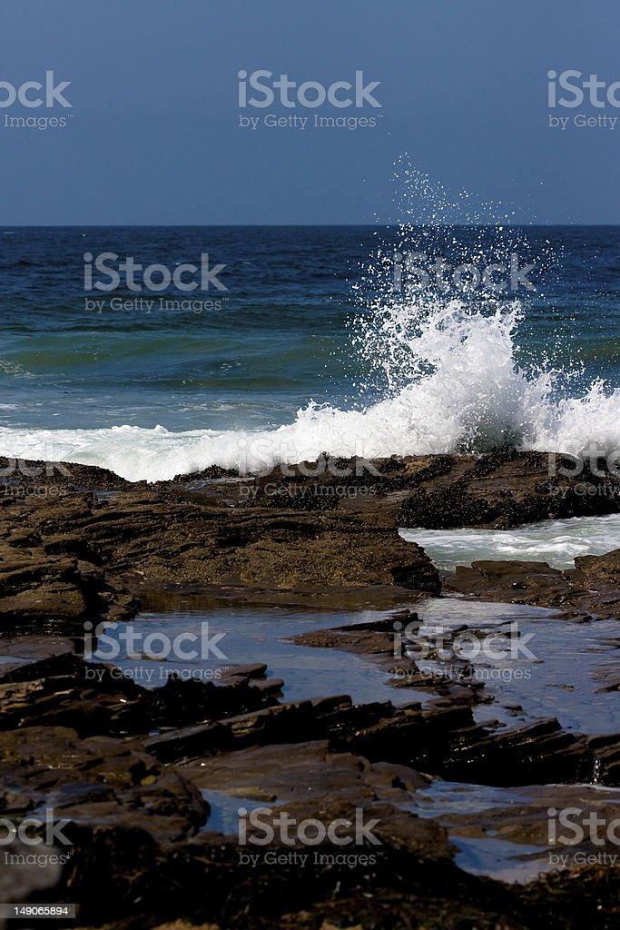 blue ocean splash onto tide pool rocks stock photo
