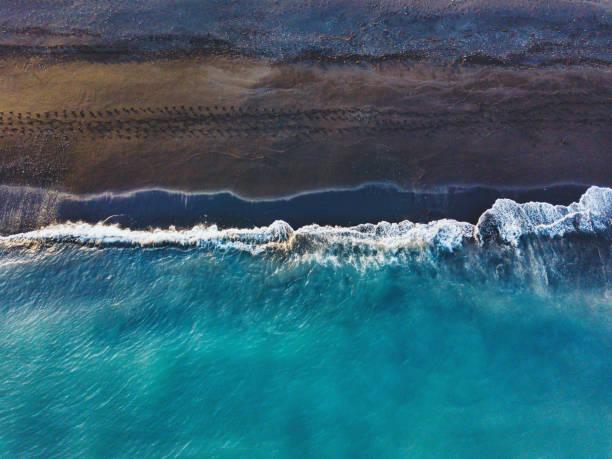 Blaue Ozeanwelle am schwarzen Sandstrand in Island – Foto