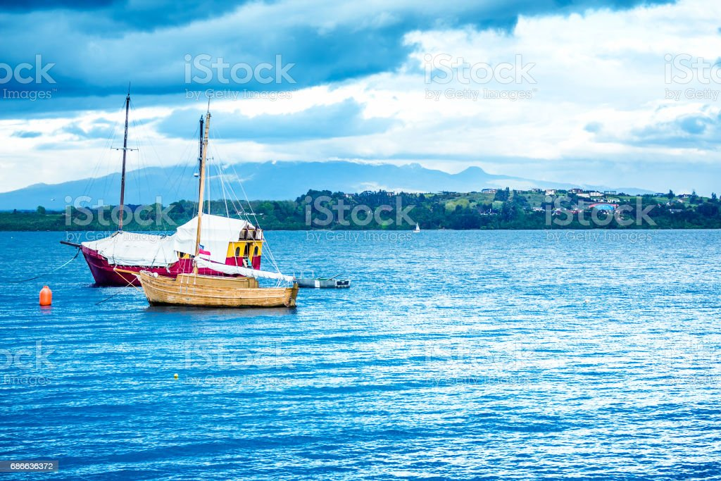 Blue ocean with boats and coastline stock photo