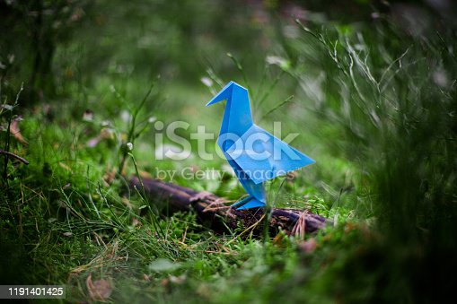 Blue, made of paper origami bird sitting on the fallen branch in forest