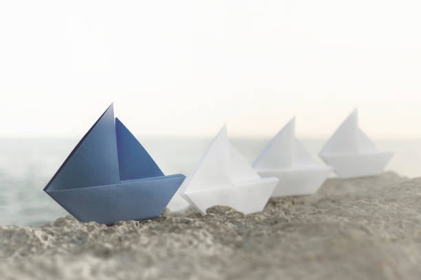 blue origami ship is the leadership of all white ships, a good business teamwork concept stock photo