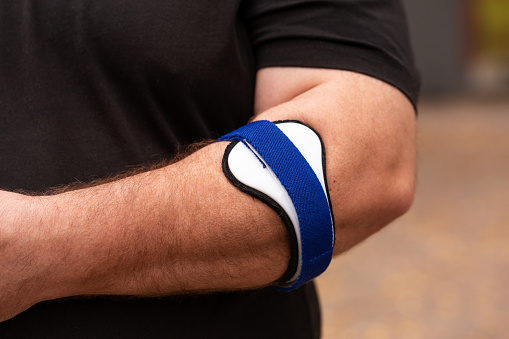 Blue orthosis using for tennis elbow therapy
