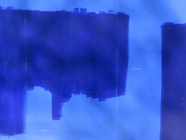 blauwe verf op een lichtere blauw geschilderde muur die door de zon wordt aangestoken foto