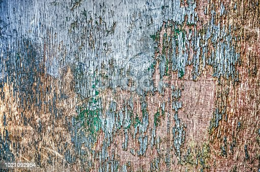 close-up of a piece of weathered plywood with greenish blue paint in an advanced state of exfoliation
